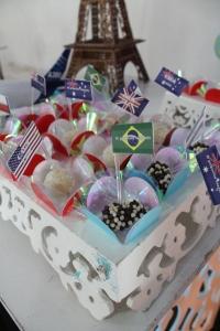 Mesa de docinhos com tags de bandeirinhas de vários países SomosdoMundo